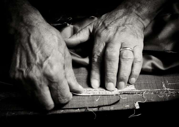 Close up of a older man at work as a tailor.